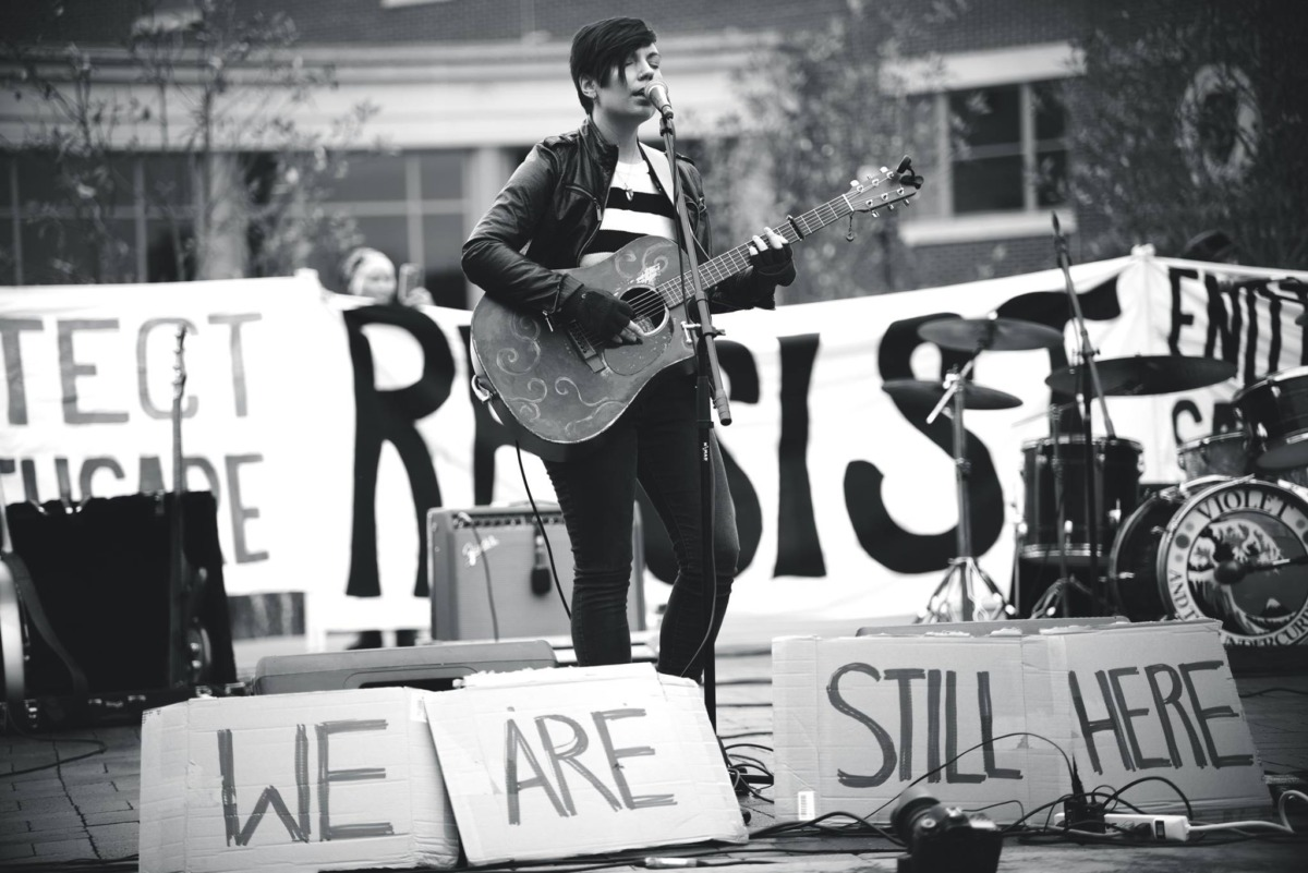 A musician stands with a guitar among many protest signs.